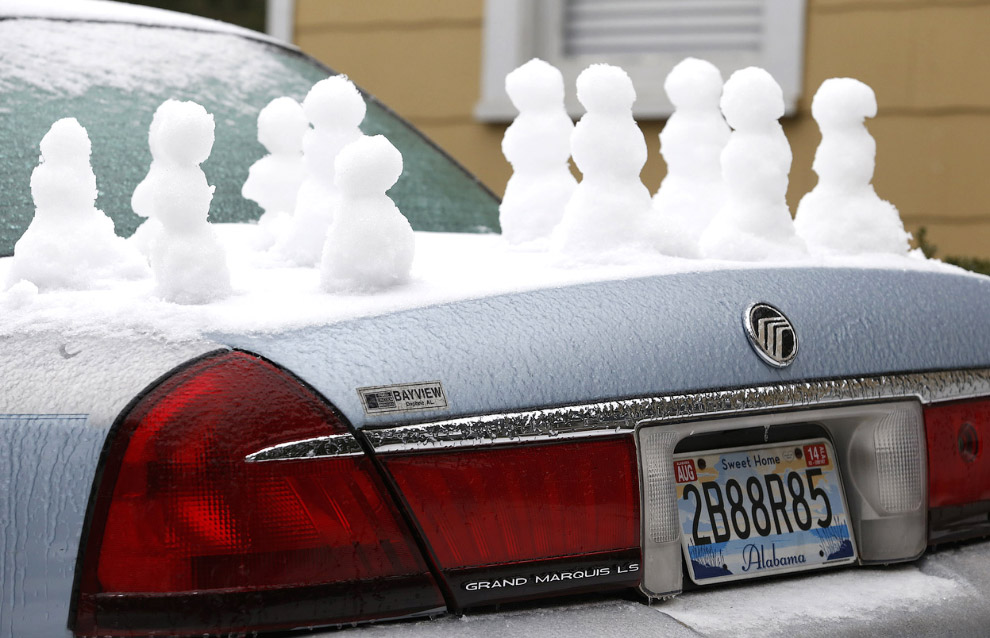 Покрытые ледяной коркой машины — последствия ледяного дождя в штате Алабама, 29 января 2014. Впрочем, народ не унывает и лепит снеговиков