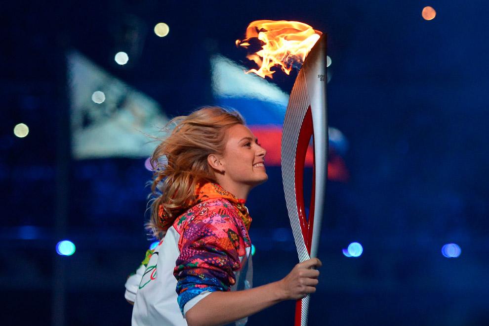 Феерическое представление закончилось. На арене появляются спортсмены и несут факел к чаше, чтобы зажечь огонь Игр. Первой была теннисистка Мария Шарапова