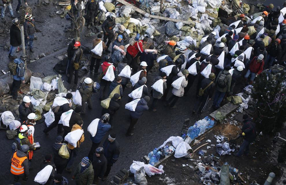 Вот несут мешки с камнями для постройки баррикад вокруг Майдана Независимости