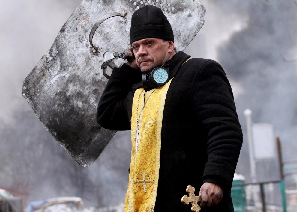 Священник держит крест и щит во время столкновений между участниками антиправительственных демонстраций и милицией в центре Киева, Украина