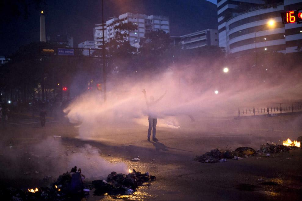Демонстрант против водяной полицейской пушки, Каракас
