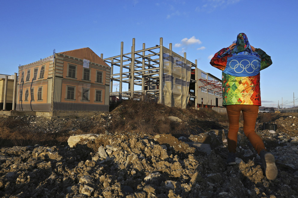 Волонтер Игр и одно из недостроенных зданий