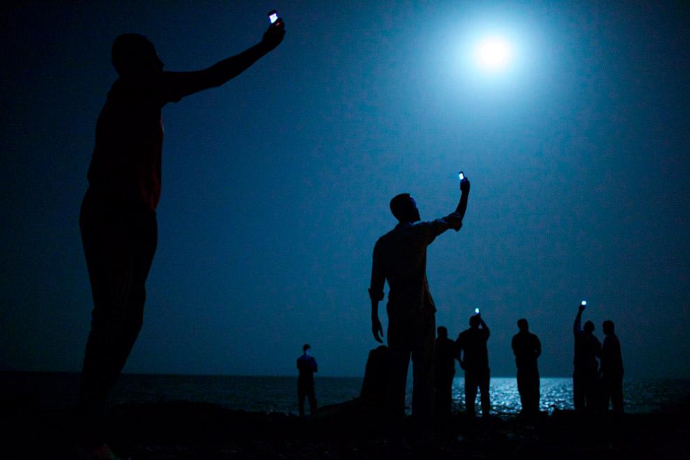 На фотографии африканцы в столице Джибути — перевального пункта для беженцев из Сомали и Эфиопии, которые направляются в Европу и Ближний Восток. Они стараются поймать сигнал сомалийского сотового оператора, чтобы сообщить близким, что с ними все в порядке. Тысячи таких африканцев умирают в пути