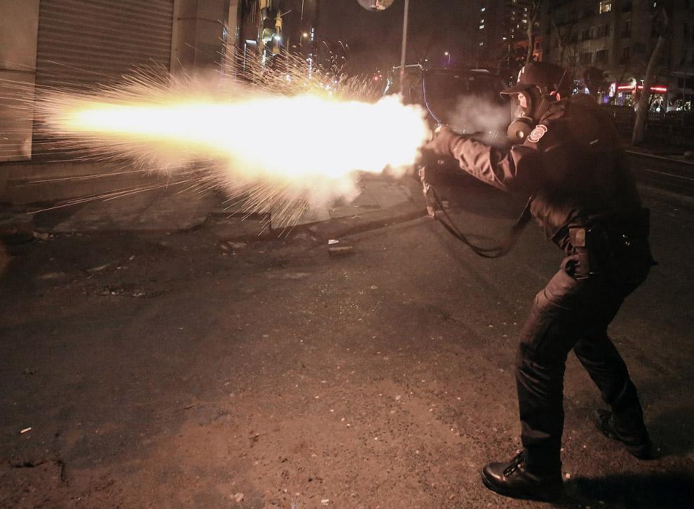 Полицейский стреляет в сторону протестующих. Из чего — непонятно