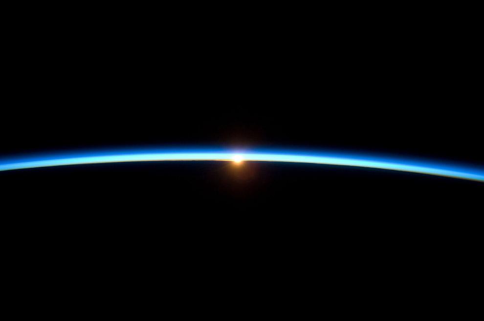 Тонкая линия земной атмосферы и заходящее Солнце