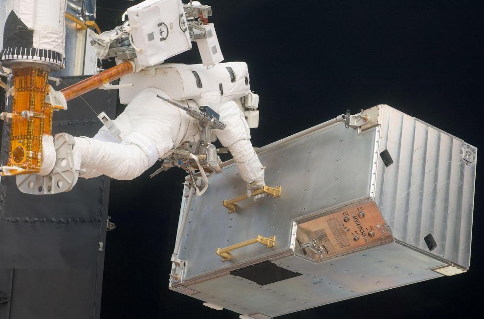 Астронавт Эндрю Фьюстел с корректирующей оптикой COSTAR во время сервисной миссии на телескопе Хаббл