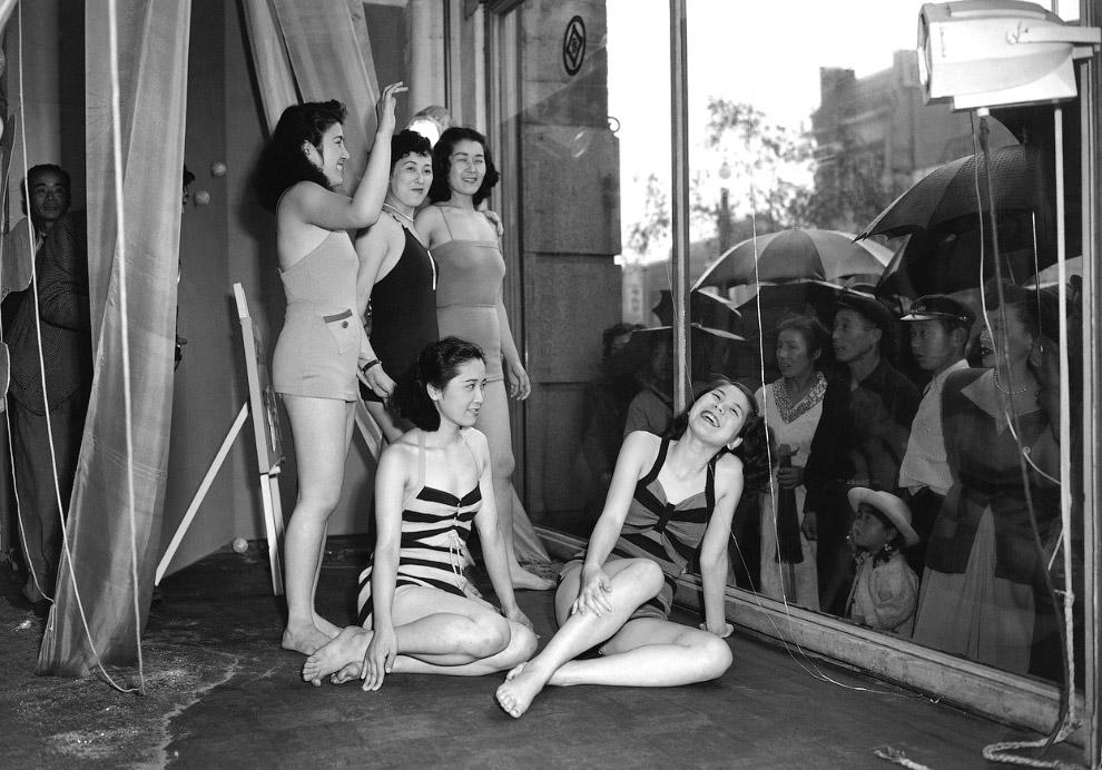 Универмаг Токио и модели рекламируют модные купальные костюмы