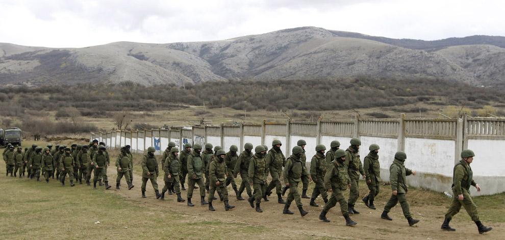 Люди у униформе, которых считают российскими военнослужащими, около военной базы в селе Перевальное возле Симферополя