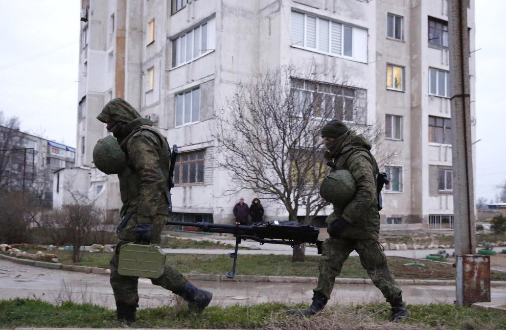 Предположительно российские солдаты несут тяжелый пулемет около украинской военной базы в Евпатории