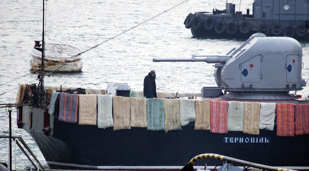 """Украинский моряк наблюдает за российскими солдатами, пытающимися захватить судно """"Тернополь"""" в Севастополе, 4 марта 2014. Украинцы кладут одеяла и матрасы на борт кораблей, чтобы воспрепятствовать любой попытке нападения"""