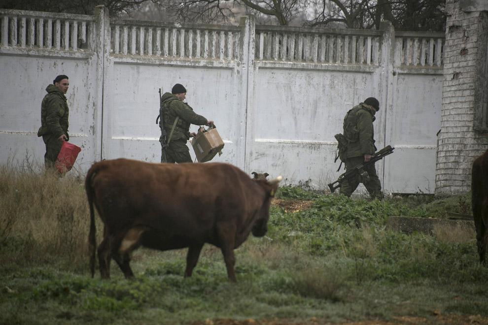 Люди у униформе, которых считают российскими военнослужащими, возле украинской военной базы в Севастополе