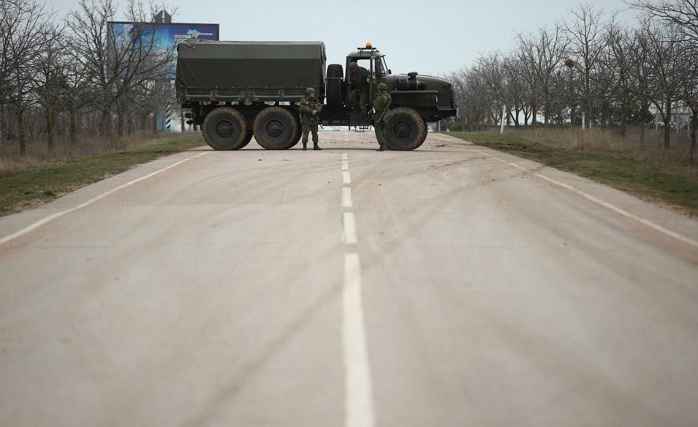 Солдаты блокируют дорогу, ведущую к аэропорту Бабек в районе Севастополя, по-видимому, занятый российскими войсками