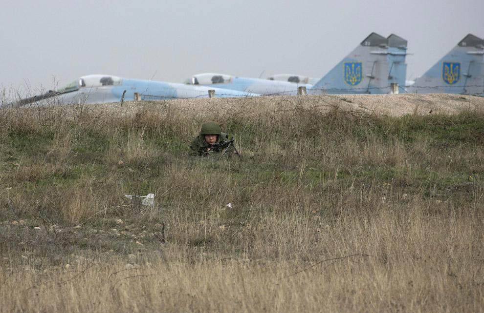 Русский солдат на фоне украинских истребителей в аэропорту Бельбек, Крым