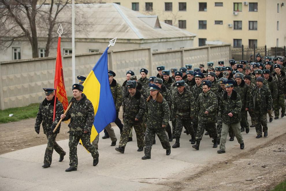 Украинские войска с украинским флагом идут навстречу российским солдатам, оккупировавшим авиабазу Бельбек