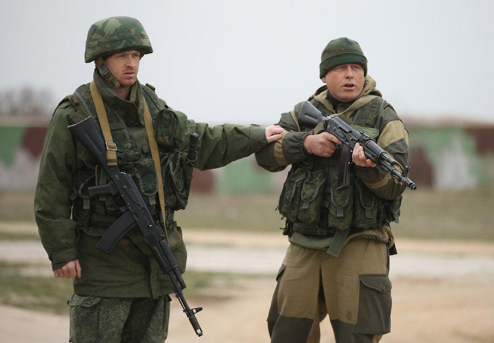 Один российский военный сдерживает другого, стрелявшего в воздух и приказывающего повернуть назад группе из более чем 100 невооруженных украинских солдат возле авиабазы Бельбек