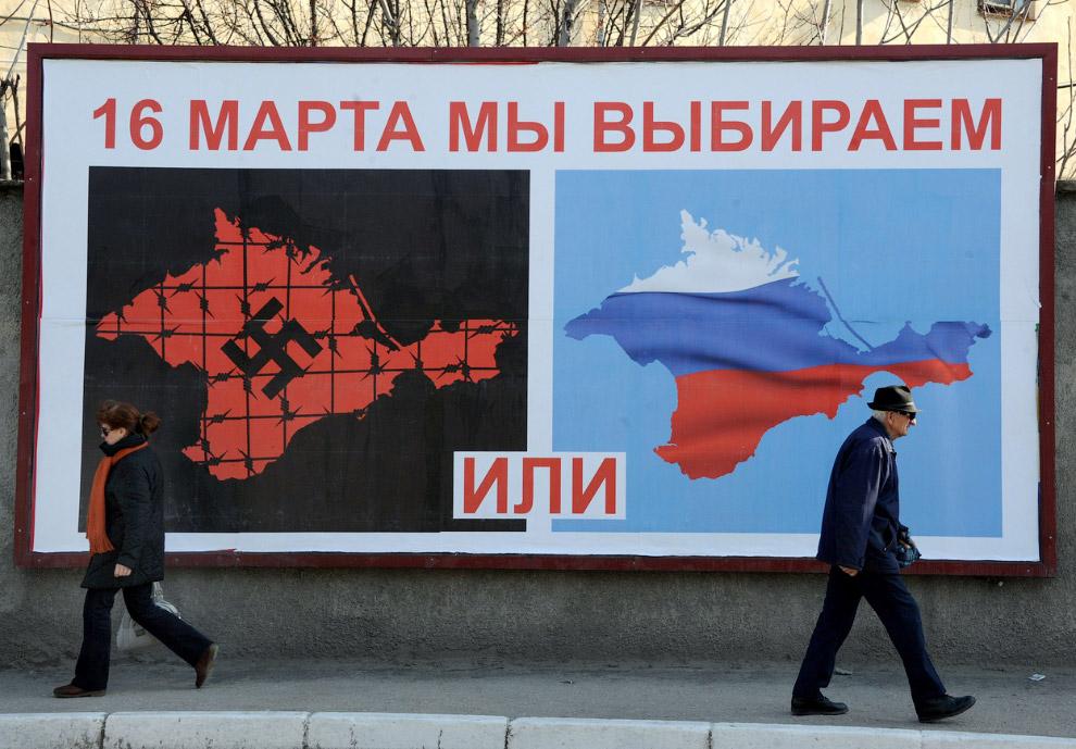 Плакат на улице Севастополя перед референдум в эти выходные, изображающий Крым со свастикой и покрытый колючей проволокой, и Крым с цветами российского флага