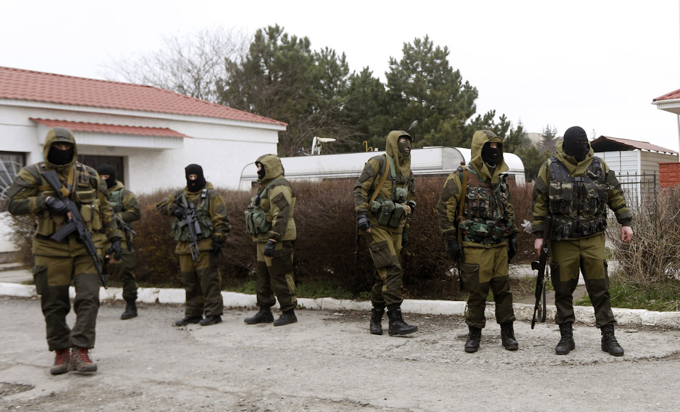 Вооруженные люди, предположительно российские военнослужащие, стоят у входа воинской части в Симферополе