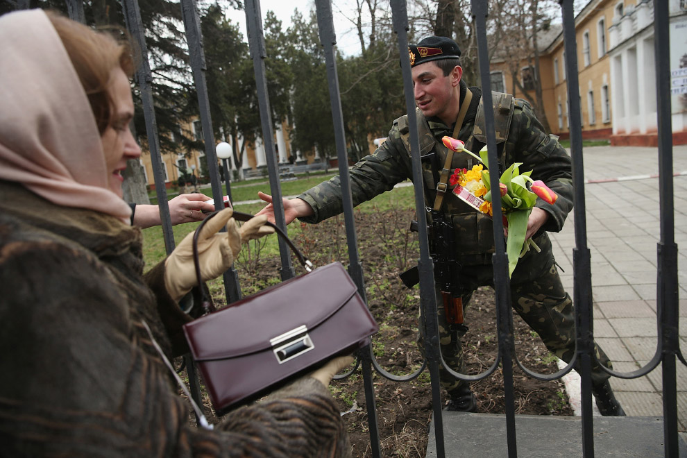 Украинский солдат принимает через забор блокированной украинской военной базы сигареты, шоколад и цветы
