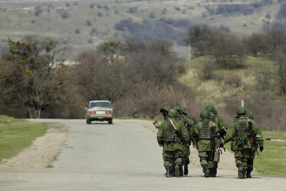 Вооруженные люди, предположительно российские военнослужащие, идут недалеко от военной базы в селе Перевальное
