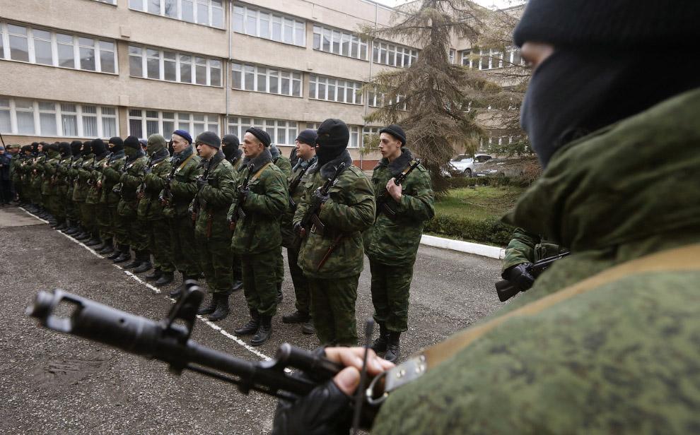 Вооруженный человек, предположительно российский военный (справа), и пророссийский отряд самообороны во время присяги на верность крымскому правительству