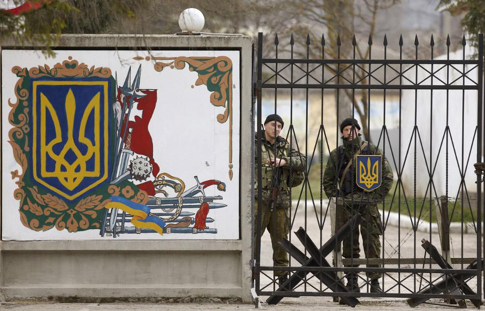Украинские офицеры стоят за воротами воинской части в поселке Перевальное, 11 марта 2014. Пророссийские войска открыли огонь и захватили украинского военную базу в Крыму