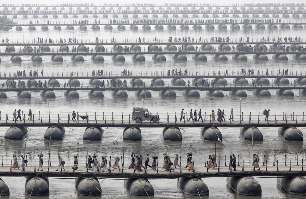 Паломники на понтонных мостах во время Маха Кумбха Мела, Индия. Кумбха-мела («праздник кувшина») — обряды массового паломничества индусов к святыням индуизма, приводящиеся с периодом в 6 или 12 лет.