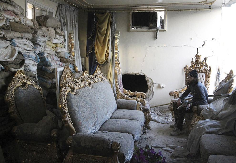 Боевик в разрушенном доме в старом городе Алеппо