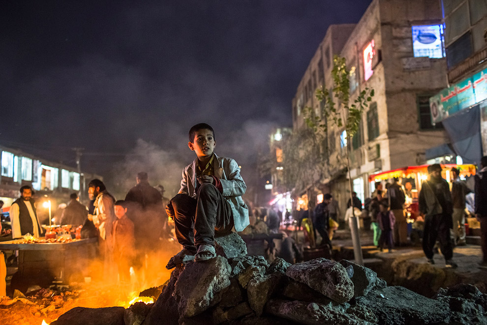 Афганский мальчик греется на улице от огня в старом части Кабула