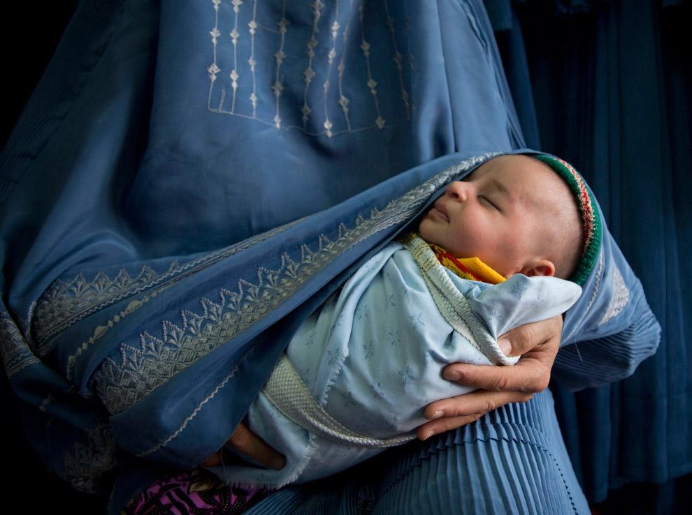 Покупательница с новорожденным в магазине по продаже паранджи
