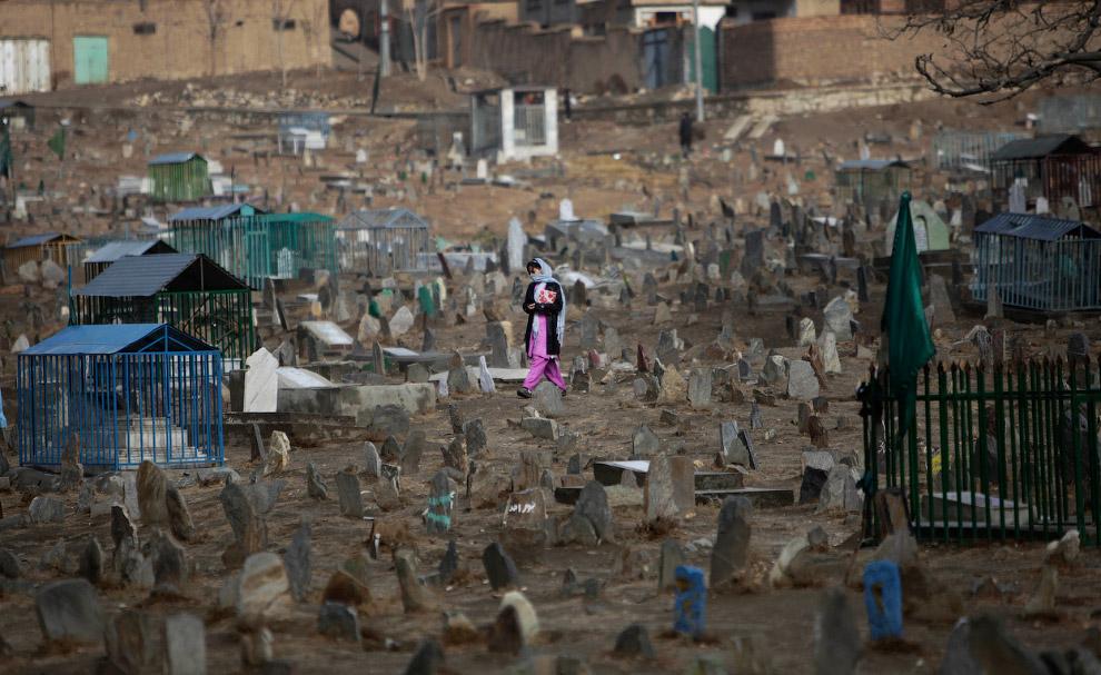 Афганская девочка идет по кладбищу на окраине Кабула