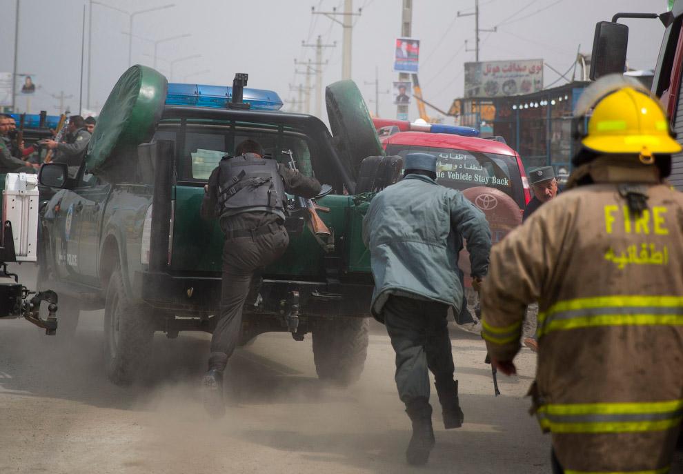 Афганские полицейские на ходу садятся в автомобиль