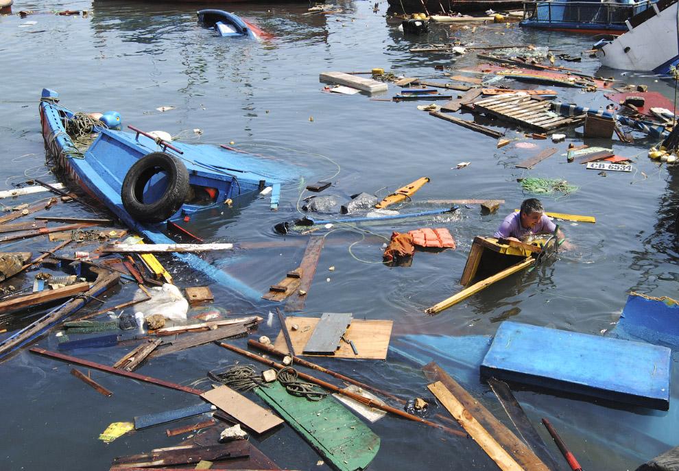 Рыбак пытается спасти имущество со своей лодки
