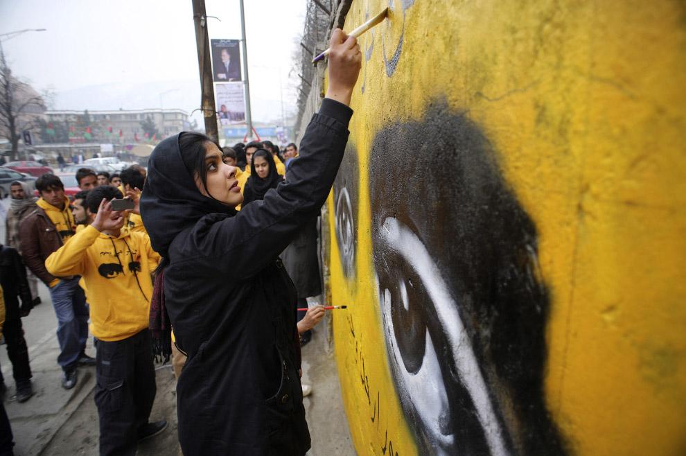 Афганский общественный деятель рисует граффити на стене здания министерства образования в Кабуле