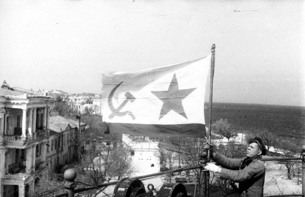 Морской пехотинец устанавливает советский военно-морской флаг в освобожденном Севастополе