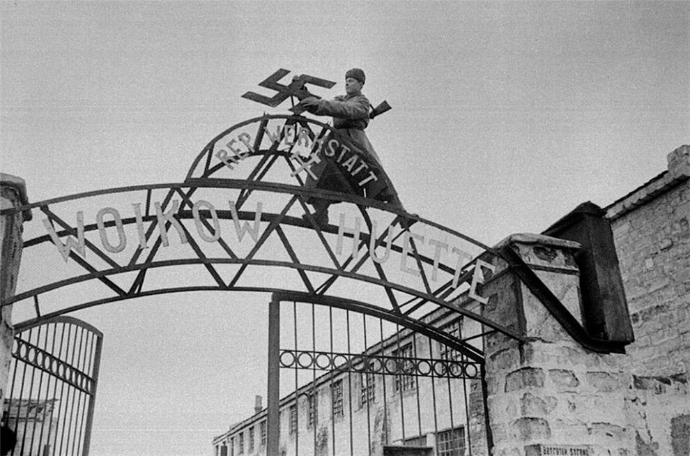 Советский солдат срывает нацистскую свастику с ворот  металлургического завода им. Войкова в освобождённой Керчи