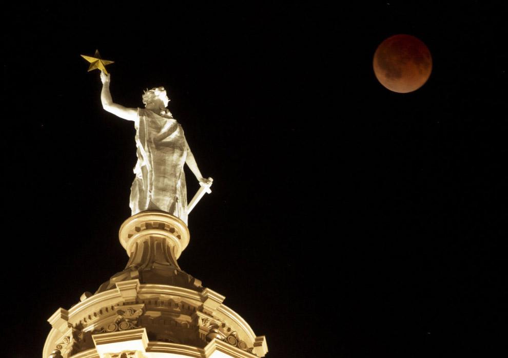 А это снимок лунного затмения на фоне Статуи свободы наверху Капитолия в Остине, штат Техас