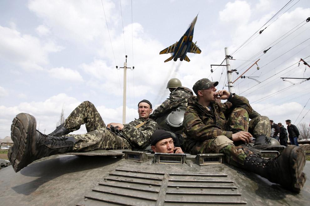 Украинские солдаты на бронетранспортере и украинский истребитель в Краматорске на востоке Украины