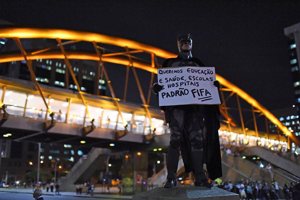 Бэтман с плакатом: «Нам нужны образование, здравоохранение, школы и больницы»