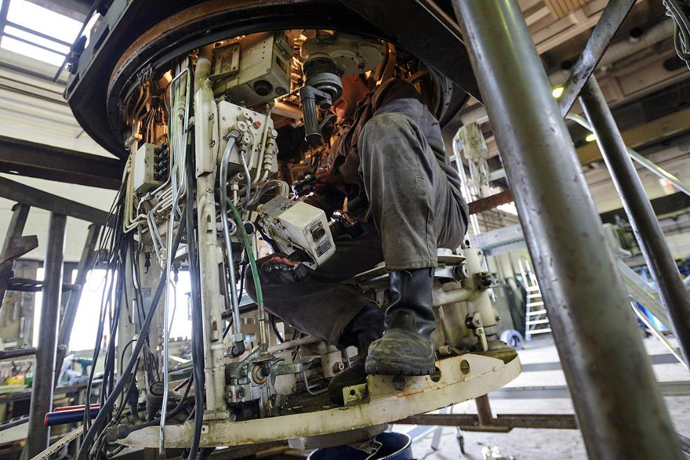 Рабочие компании разбирают танки по запчастям