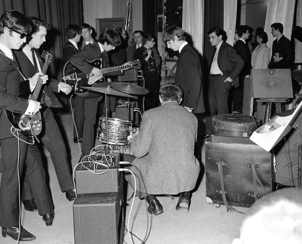 Слева — Джон Леннон, по центру с гитарой — Джордж Харрисон и Ринго Старр