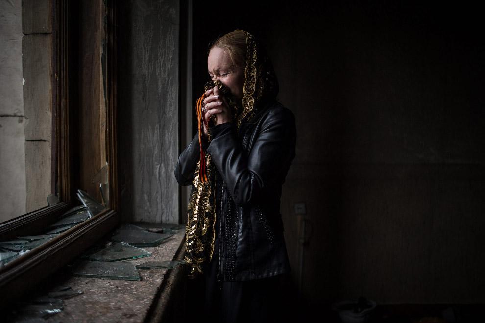 Плачущая женщина с георгиевской ленточкой внутри здания Дома профсоюзов в Одессе