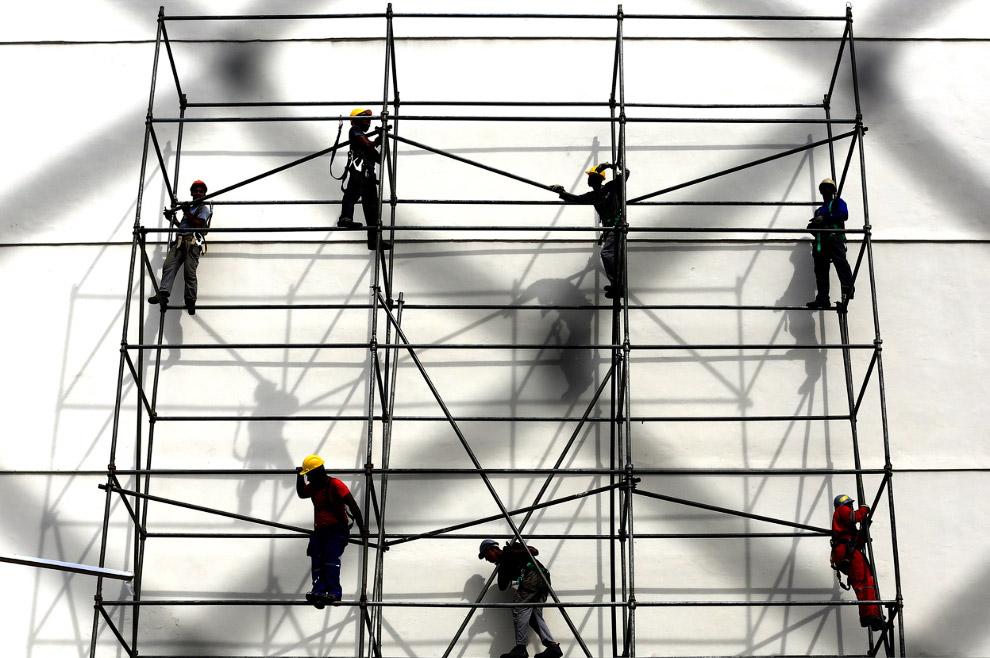 Рабочие доделывают фасад стадиона «Маракана́»