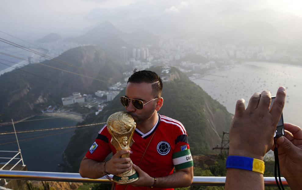 Болельщик из Колумбии с копией Кубка мира на вершине горы Сахарная голова