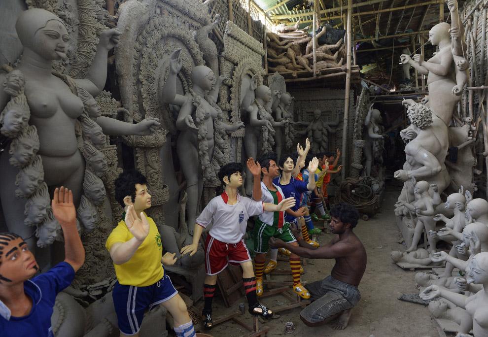 Индийский скульптор дает глиняные модели футболистов в мастерской в Калькутте