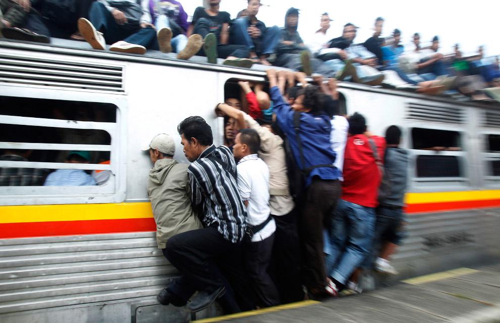 Индонезийские пассажиры уплотняются в поезде в провинции Западная Ява
