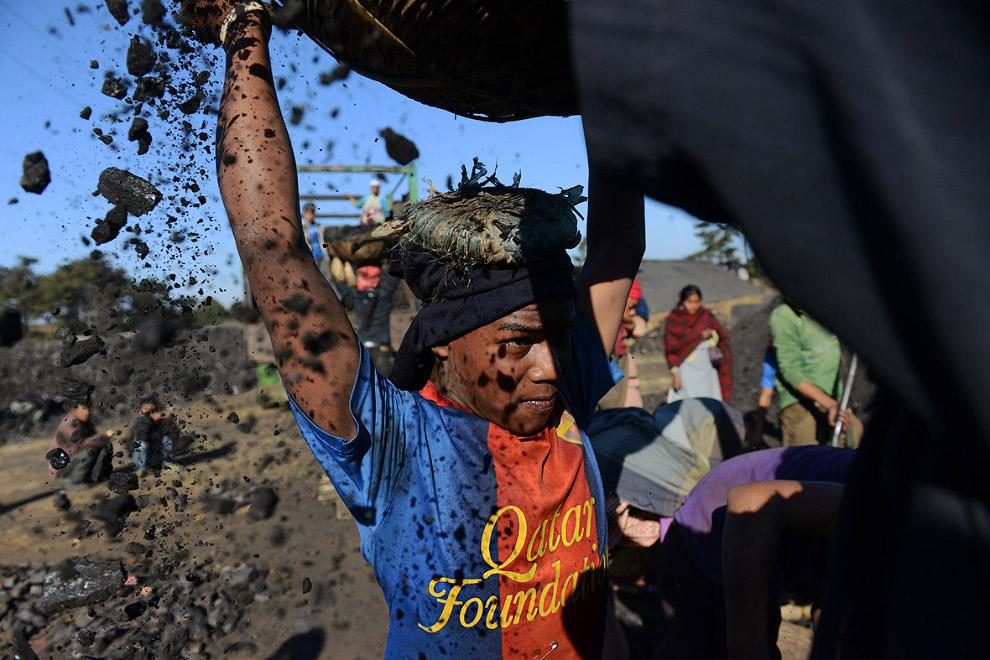 Работник поднимает корзину с углем в транспортное средство
