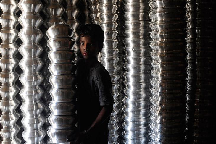 Работник фабрики по производству алюминиевой посуды