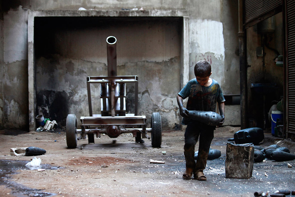 10-летний мальчик тащит минометный снаряд. Алеппо, Сирия