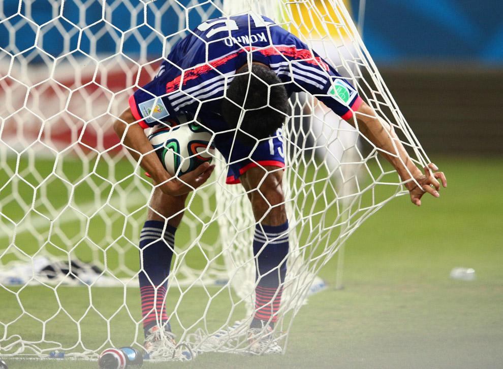 Удрученный вратарь сборной Японии вынимает мяч из своих ворот