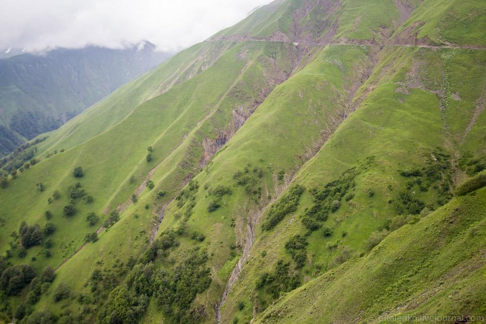 На склонах гор вырезана дорога. Встречную машину видно издалека